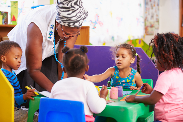 African American preschool children and teacher in school