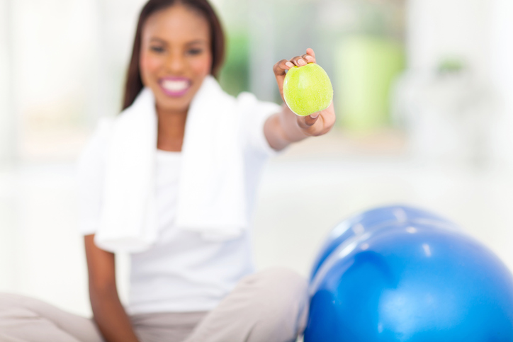 African American woman with apple and exercise ball