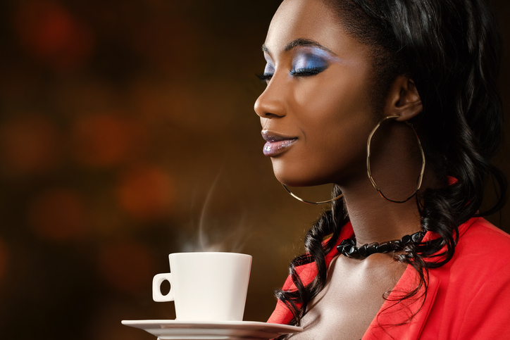 African American woman smelling coffee