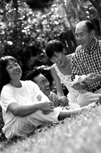 Photo of family enjoying a picnic on the grass.