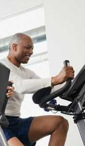 older african american man exercising on a stationary bike