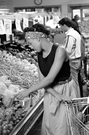 Photo of a woman shopping for vegetables in a grocery store.