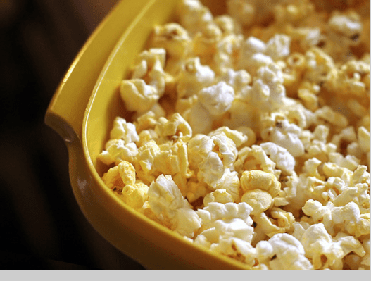 A yellow baking dish filled with buffalo-flavored popcorn