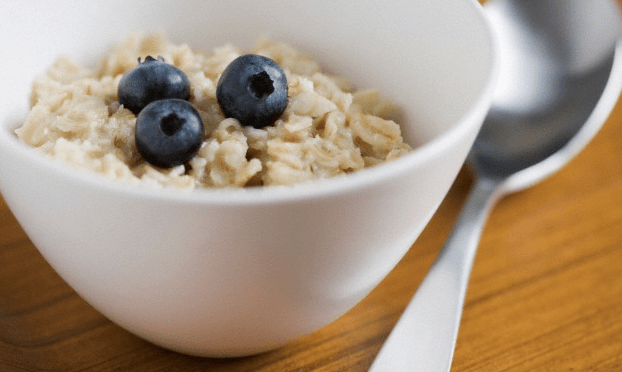 A bowl of oatmeal with three blueberries