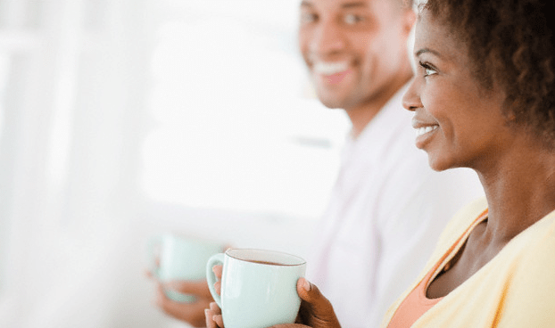 A smiling couple holding matching mugs of coffee