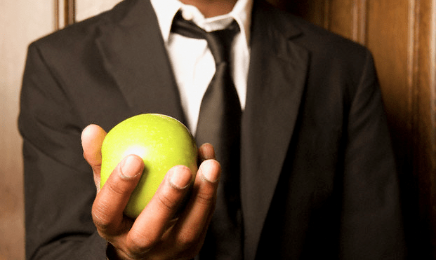A man in a suit holding an apple