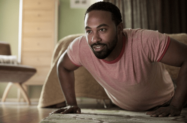 A smiling man doing pushups in his bedroom