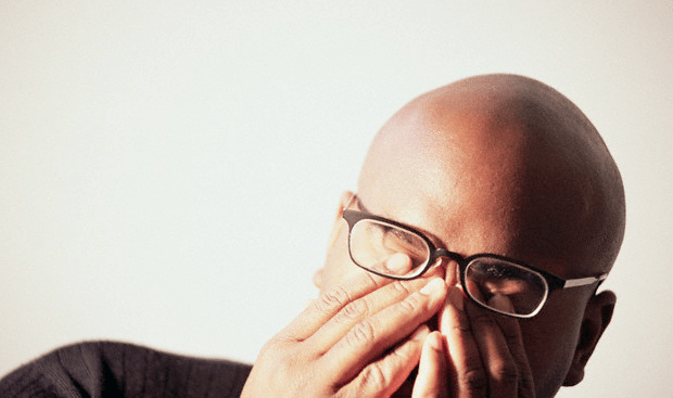 A man with glasses rubbing his eyes