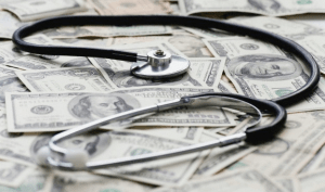A stethoscope sitting on a pile of money
