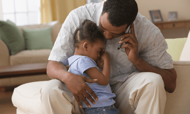 A father hugging his upset little girl while talking on a cell phone