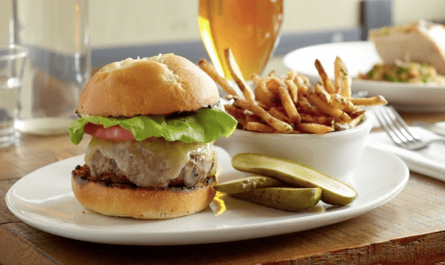A gourmet burger, bowl of fries and a glass of beer at a table at a nice restaurant