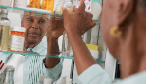 A senior woman reaching into her medicine cabinet for a prescription bottle