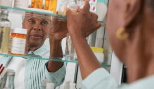 A senior woman reaching into her medicine cabinet for a prescription bottle