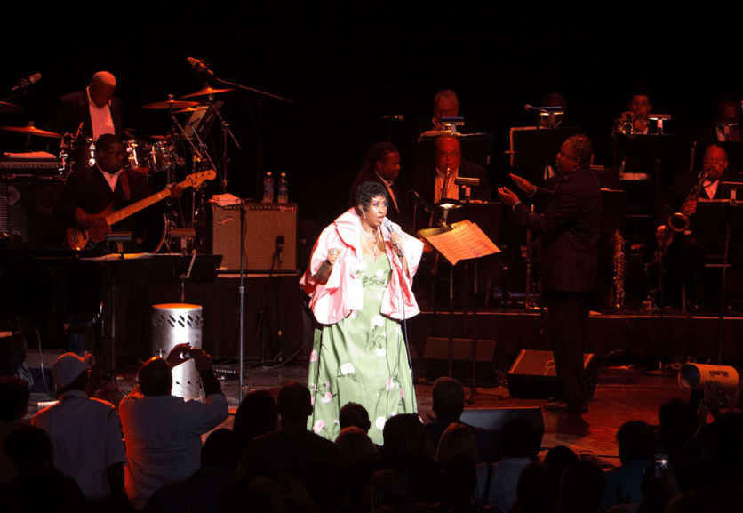 Aretha Franklin performing with a band in a concert