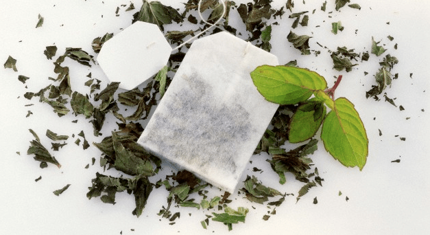 A tea bag sitting on top of loose tea leaves on a white surface