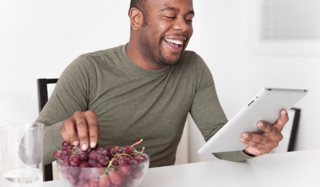 man eating grapes while holding an ipad