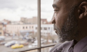 older african american man looking out of window