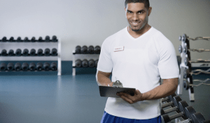 A smiling personal trainer with a clipboard