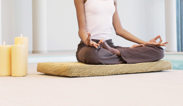 A woman in a yoga pose on a cushion next to lit candles