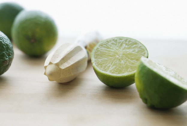 Three limes and a juicer sitting on a wooden surface