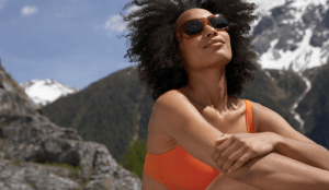 A woman with natural hair posing near mountains, wearing sunglasses