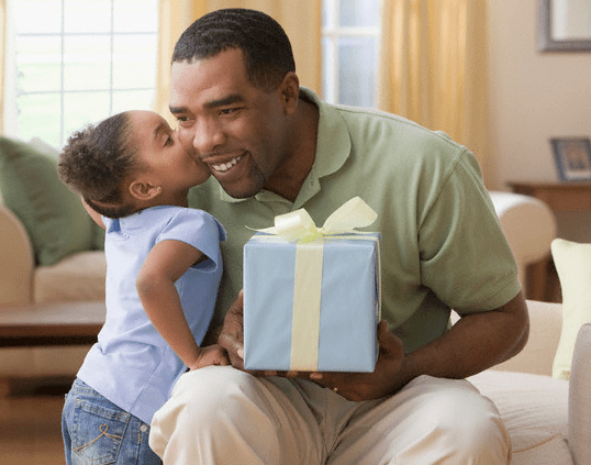 A little girl kissing her father on the cheek as he holds a Father's Day gift in a wrapped box