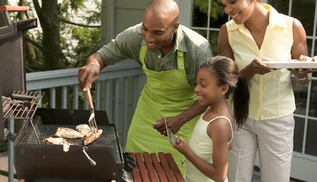 A family standing with plates in front of a grill