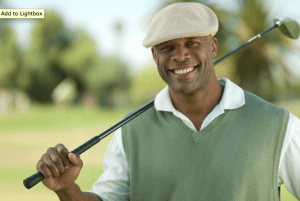 A smiling man wearing a golf hat and holding a golf club