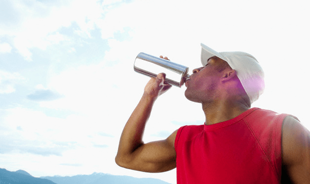 A man drinking from a metal water bottle