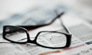 A pair of eye glasses sitting on a newspaper