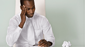 A sick man sitting at his desk and looking at a crumpled piece of tissue