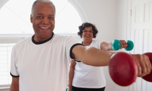 An older couple lifting weights in their home