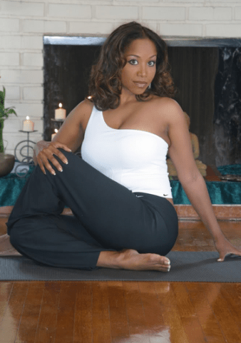 Robin Downes posing on a wood floor in a yoga position