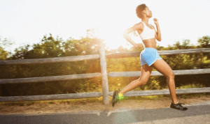 A woman in shorts running outside with the sun in the distance