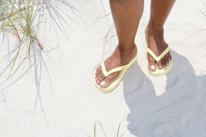 A woman's feet wearing yellow flip flops in the sand