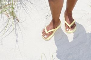 A woman's feet wearing yellow flip flops in the sand