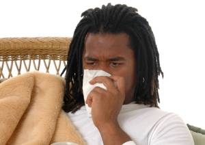 young black man blowing nose