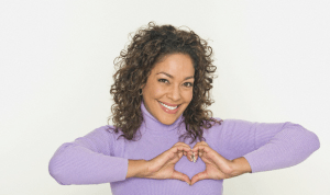 african american woman wearing a purple turtleneck making a heart symbol with the hands over her heart