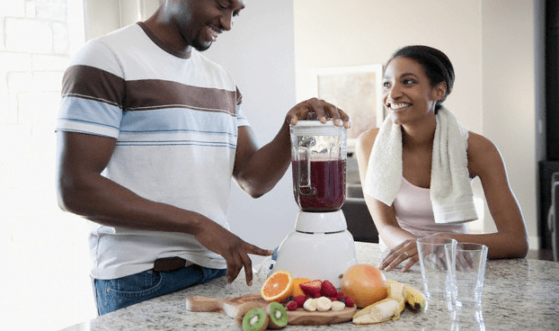 A man making smoothies in a blender while a woman looks at him