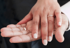 A married couple's hands on top of each other, both wearing wedding rings