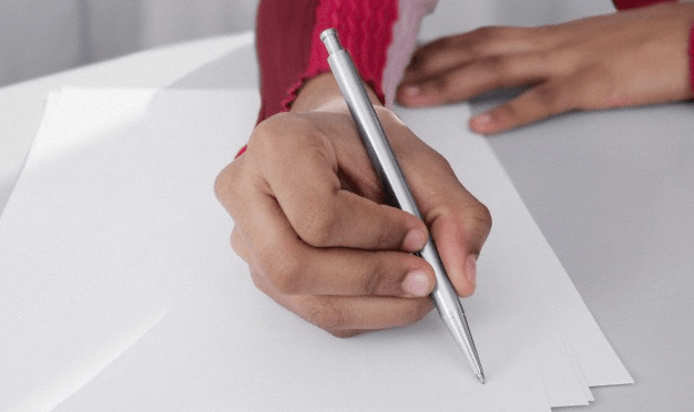 A close-up of a woman's hand holding a pen over pieces of paper