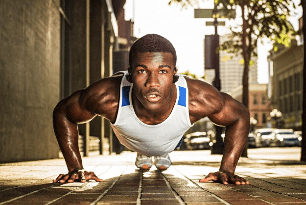 A man in the pushup position in the street