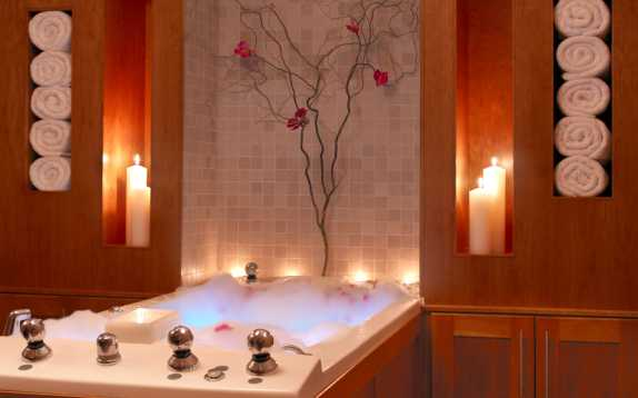 Candles and towels surrounding a bubble bath