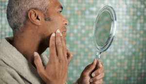 A man looking at a patch of his skin using a handheld mirror