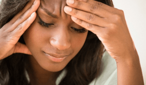A woman with a headache touching her forehead