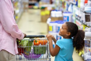 african american girl holding on to a cart in grocery store