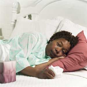 woman laying in bed with tissue