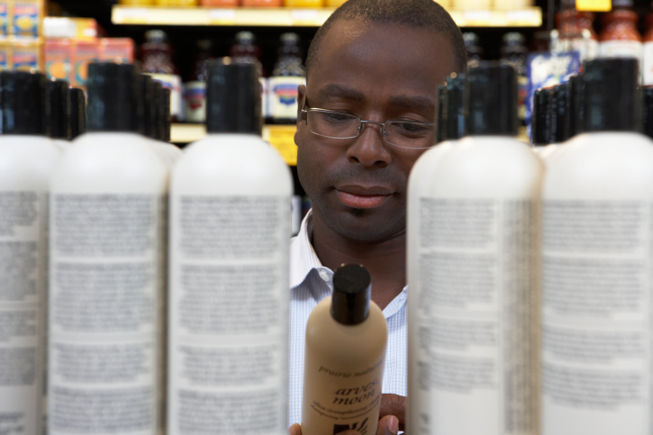 man reading shampoo labels