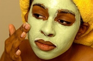african american woman putting on facial mask