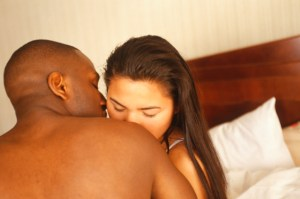 young couple in bed, being intimate